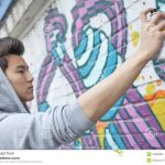 Serious Young Man Concentrating While Holding Spray Can Painting Wall